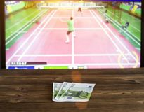 Euro money on the background of TV on which goes badminton, betting office, sports betting. Shuttlecock stock photo