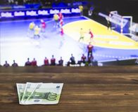Euro money on the background of the TV on which show handball, sports betting, handball and euro. Euro money on the background of the TV on which show handball royalty free stock photos