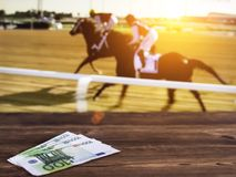 Euro money on the background of a TV on which show jumps on horses, sports betting, races, euro. Euro money on the background of a TV on which show jumps on royalty free stock photography