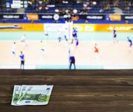 Euro money on the background of the TV on which show volleyball, sports betting, bookmaker, euro. Euro money on the background of the TV on which show volleyball royalty free stock image