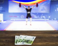 Euro money on the background of TV on which show weightlifting, sports betting, bookmaker. Euro money on the background of TV on which show weightlifting, sports stock photo