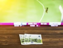Euro money on the background of the TV on which there is a sports game of cricket, sports betting, euro. Euro money on the background of the TV on which there is royalty free stock image