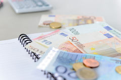 Euro money banknotes and coins counting with calculator, notebook Royalty Free Stock Image
