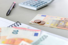 Euro money banknotes and coins counting with calculator, notebook and pen Stock Image