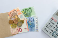 Euro money banknotes and coins counting with calculator Stock Images