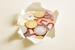 Euro money behind hole in paper Stock Photos