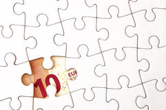 Euro money bill under jigsaw puzzle Royalty Free Stock Images