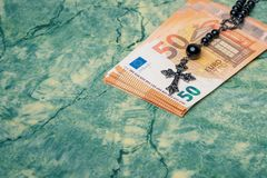 Euro money and black rosary. Black rosary and euro money on green table,concept photo royalty free stock images