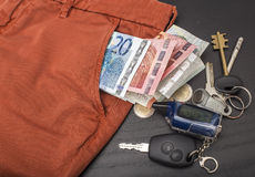Euro money and coins fell out of his pocket on the table, on which lie the keys Stock Photography