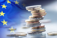 Euro money.Euro Flag.Euro currency.Coins stacked on each other in different positions. European union flag.  Stock Photos