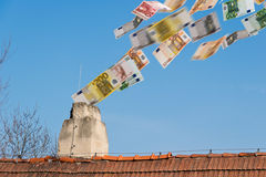 Euro money flies up the chimney Royalty Free Stock Images