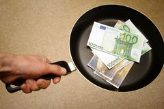Euro money on frying pan Stock Photography