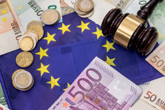 Euro money with hammer on flag Royalty Free Stock Images