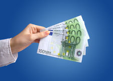 Euro money in hand. Hand holding hundred euros over blue background Stock Photography