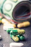 Euro money and medicaments. Euro banknotes and pills. Rolled euro banknotes stacked on each other in different positions and freely pills around scattered Stock Photo