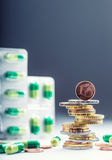 Euro money and medicaments. Euro coins and pills. Coins stacked on each other in different positions and freely pills around Stock Images