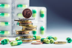 Euro money and medicaments. Euro coins and pills. Coins stacked on each other in different positions and freely pills around. Scattered. Toned image royalty free stock photography