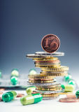 Euro money and medicaments. Euro coins and pills. Coins stacked on each other in different positions and freely pills around Stock Image