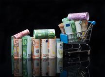 Euro money rolls and shopping cart full packs of bills. On black background with reflection. Business and financial concept with euro banknotes royalty free stock image