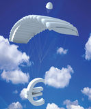Euro money symbol in sky. Euro money symbol hanging from a parachute in the blue and cloudy sky Stock Images