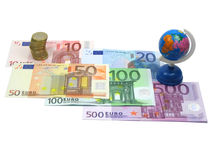 Euro money and world globe. Euro notes and coins with little world globe isolated in white Stock Image