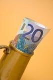 Euro mug. Euro bill inside the golden mug isolated on light brown background Royalty Free Stock Image