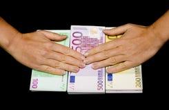 Euro munt in handen op zwarte Stock Afbeeldingen