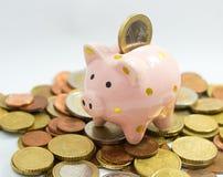 Euro muntstuk die in spaarvarken bovenop muntstukstapel vallen Royalty-vrije Stock Afbeeldingen