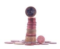 1 euro muntstuk die zich bovenop stapel euro die muntstukken bevinden op wit worden geïsoleerd Stock Foto's