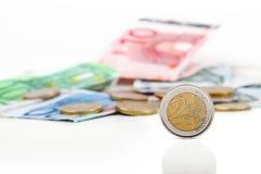Euro muntstuk met andere euro muntstukken en bankbiljetten op achtergrond Stock Afbeelding