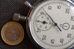 Euro muntstuk met een benaming van euro één (achterkant) en chronometer op bruine denimachtergrond - bedrijfsachtergrond Royalty-vrije Stock Afbeeldingen