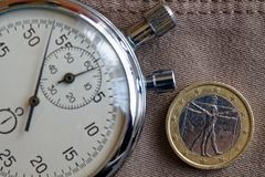 Euro muntstuk met een benaming van euro één (achterkant) en chronometer op oude beige jeansachtergrond - bedrijfsachtergrond Royalty-vrije Stock Foto's