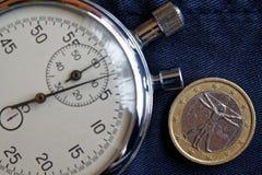 Euro muntstuk met een benaming van euro één (achterkant) en chronometer op versleten jeansachtergrond - bedrijfsachtergrond Stock Afbeelding