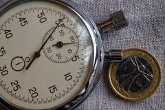 Euro muntstuk met een benaming van euro één (achterkant) en chronometer op witte vlasachtergrond - bedrijfsachtergrond Royalty-vrije Stock Foto's