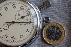 Euro muntstuk met een benaming van euro één en chronometer op grijze denimachtergrond - bedrijfsachtergrond Stock Afbeeldingen