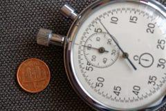 Euro muntstuk met een benaming van één eurocent (achterkant) en chronometer op bruine denimachtergrond - bedrijfsachtergrond Stock Foto