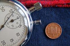 Euro muntstuk met een benaming van één eurocent (achterkant) en chronometer op versleten blauw denim met rode streepachtergrond - Stock Foto's