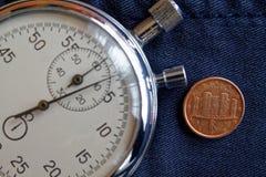 Euro muntstuk met een benaming van één eurocent (achterkant) en chronometer op versleten jeansachtergrond - bedrijfsachtergrond Stock Afbeeldingen