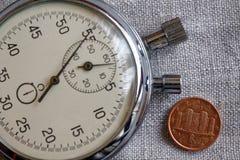 Euro muntstuk met een benaming van één eurocent (achterkant) en chronometer op witte vlasachtergrond - bedrijfsachtergrond Stock Foto's