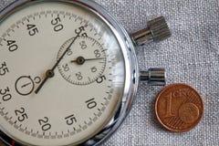 Euro muntstuk met een benaming van één eurocent en chronometer op witte linnenachtergrond - bedrijfsachtergrond Stock Foto's