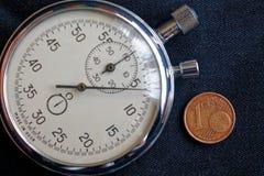 Euro muntstuk met een benaming van één eurocent en chronometer op zwarte denimachtergrond - bedrijfsachtergrond Royalty-vrije Stock Fotografie