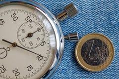 Euro muntstuk met een benaming van euro 1 en chronometer op blauwe denimachtergrond - bedrijfsachtergrond Stock Fotografie