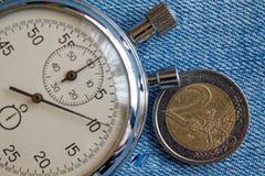 Euro muntstuk met een benaming van euro 2 en chronometer op blauwe denimachtergrond - bedrijfsachtergrond Royalty-vrije Stock Afbeeldingen
