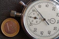 Euro muntstuk met een benaming van euro 1 en chronometer op bruine denimachtergrond - bedrijfsachtergrond Royalty-vrije Stock Foto