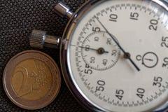 Euro muntstuk met een benaming van euro 2 en chronometer op bruine denimachtergrond - bedrijfsachtergrond Stock Afbeelding