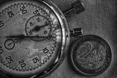 Euro muntstuk met een benaming van euro 2 en chronometer op denimachtergrond - bedrijfsachtergrond Royalty-vrije Stock Foto's