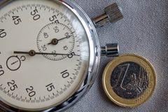 Euro muntstuk met een benaming van euro 1 en chronometer op grijze denimachtergrond - bedrijfsachtergrond Royalty-vrije Stock Afbeeldingen