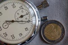 Euro muntstuk met een benaming van euro 2 en chronometer op grijze denimachtergrond - bedrijfsachtergrond Stock Afbeelding