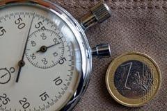 Euro muntstuk met een benaming van euro 1 en chronometer op oude beige jeansachtergrond - bedrijfsachtergrond Royalty-vrije Stock Afbeeldingen