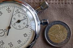 Euro muntstuk met een benaming van euro 2 en chronometer op oude beige jeansachtergrond - bedrijfsachtergrond Stock Foto's